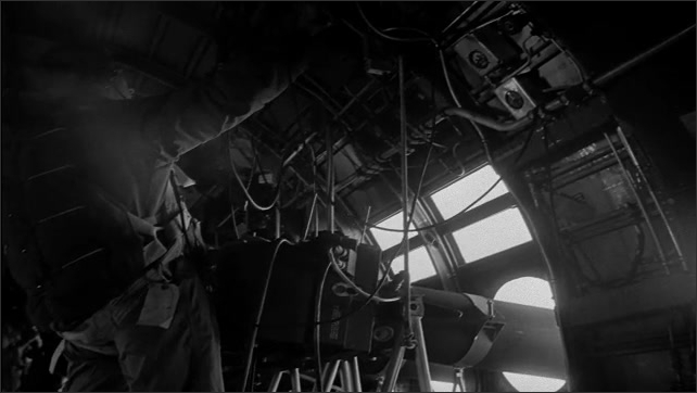 1940s Bikini Atoll: Man looks outside of plane, adjusts instrument, attaches cables to instrument. Man looks through viewfinder of camera. Film slate. Plane flies through sky.