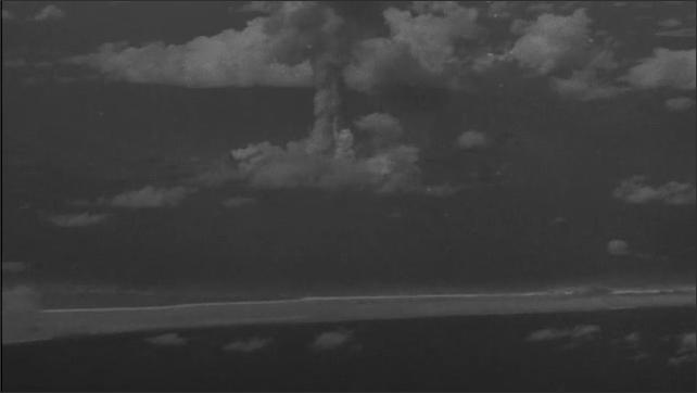 1940s Bikini Atoll: Mushroom cloud rises over island.