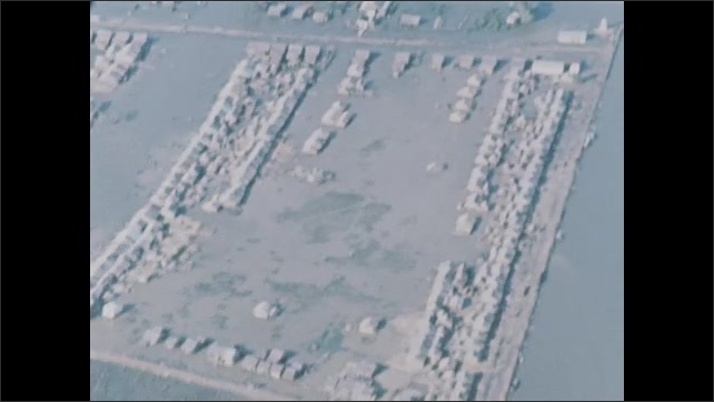 1960s: Flying in helicopter as bullets from machine gun pepper ground below. Flying over houses, buildings, structures.