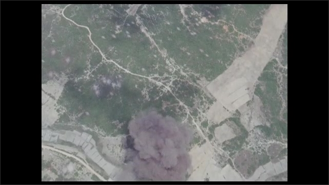 1960s: View of land from sky. Smoke rises from land. Bursts of fire on land.