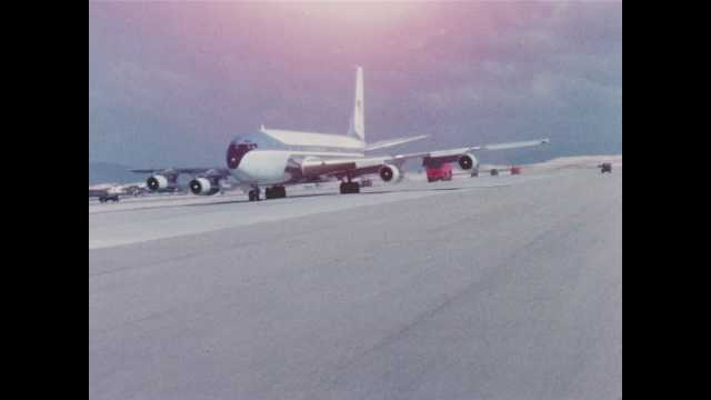 1960s Vietnam: Tracking shot of plane taxiing on runway. Plane passes by camera.