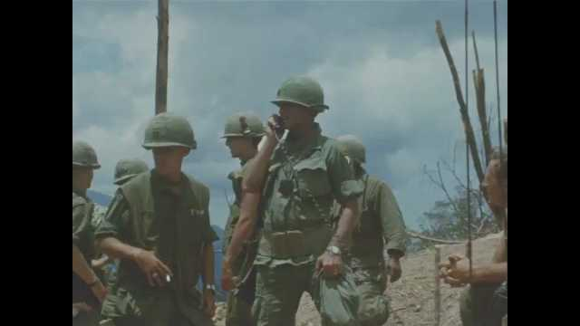 1960s Vietnam: Soldiers stand and talk on radio.  Mountains.  Airplane.