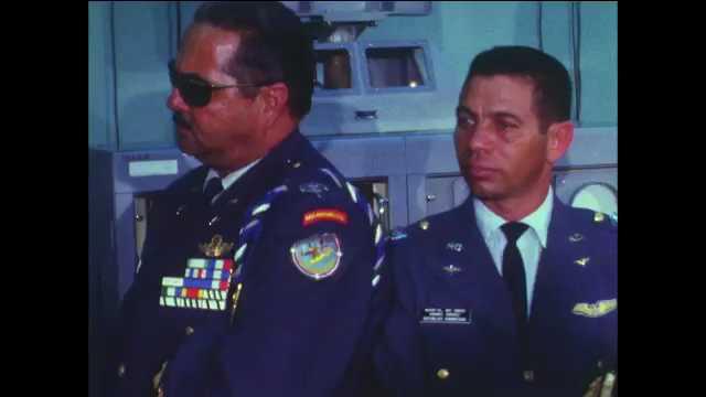 1960s: Men in military uniforms congregate in room around man talking. Men in uniforms. Film slate.