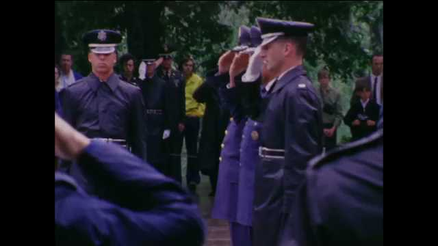 1960s: Soldiers stand at attention saluting, at funeral service. Officers carry wreath to center of ceremony area.