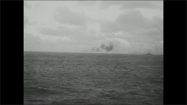 1940s: Black smoke rises from water. Clouds hang over water.