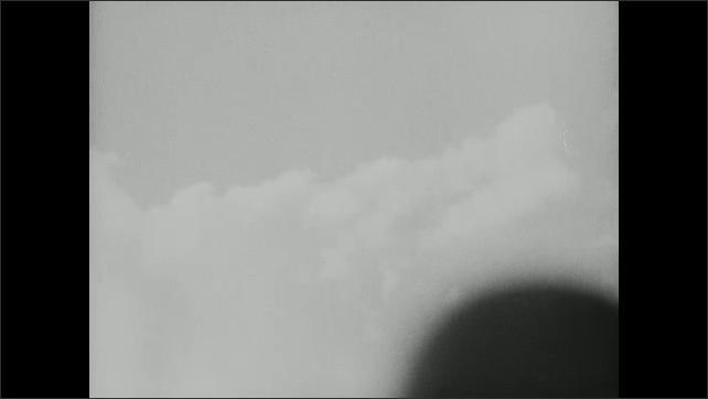 1940s: View of sky. Airplane flies past dark plume of smoke. Ship on water.
