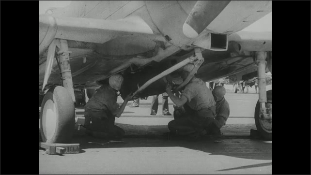 1940s: Men working under belly of plane. Man pulls dolly from under plane. Men lift missile into place under plane.