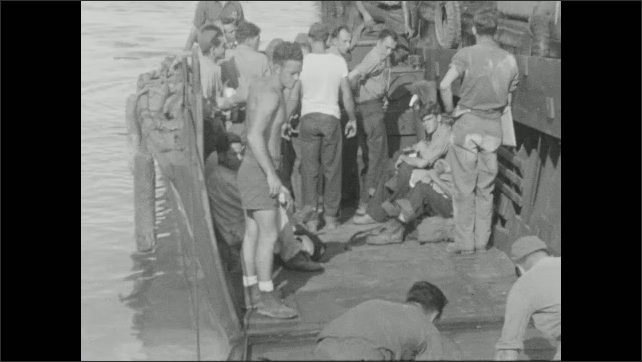 1940s: Group of soldiers carry bundles onto boat.