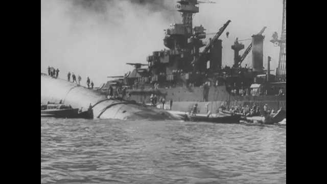 1941 Pearl Harbor: Tracking shots from water, sailors standing on destroyed ship. View of ship. Long shots of burning ships, smoke.