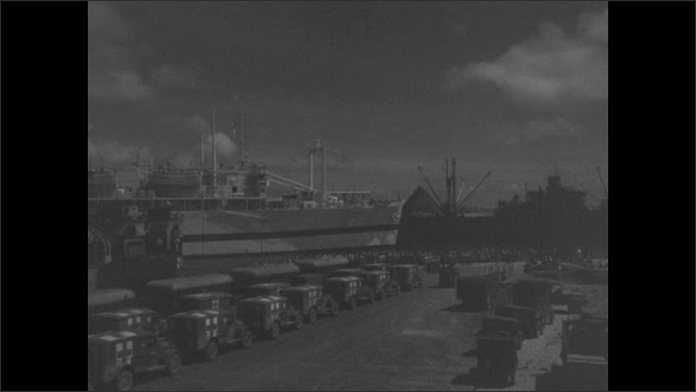 1940s: battleship sailing past other boats and people on dock
