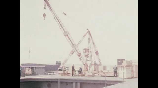 1940s San Diego: Long shot, sailors on dock, crane lifting crates.
