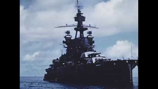 1940s Bikini Atoll: Naval Destroyer on ocean. Naval ships moored in ocean next to buoys. Sailor in white cap looks to sea.