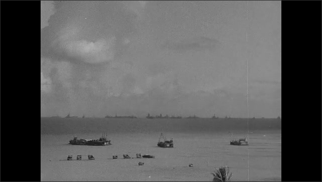 1940s: Boats sit stationary in ocean with fleet of Navy ships on horizon as fallout and debris from nuclear explosion settles in distance.