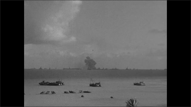 1940s: Boats sit stationary in ocean with fleet of Navy ships on horizon as fallout and debris from nuclear explosion settles in distance. Smoke rises rapidly from Navy ship.