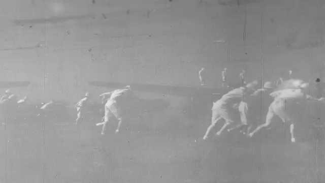 1940s Pacific Ocean: Trucks drive down runway past soldiers refueling bomber planes. Clock on wall. Soldier walks down hallway and speaks to men in room.