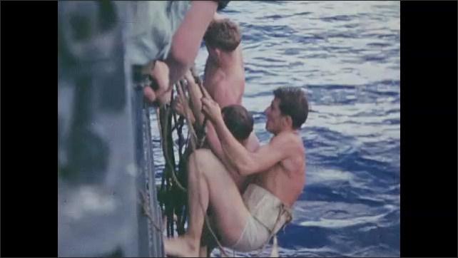1940s: Man in water next to Navy boat. Floatation device is tossed to man in water. Man uses floatation device. Men climb side of Navy boat. Navy boat at sea.