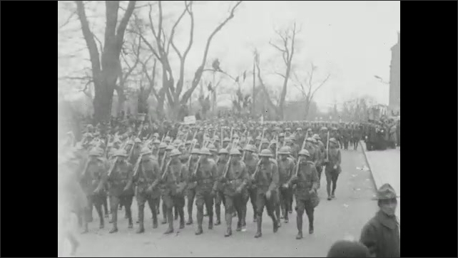 1910s: Soldiers on horseback arade down street. Crowds of people sit in stands. Soldiers march down street.