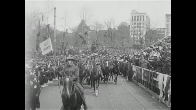 1910s: Cars with red cross flags drive down street. Men on horseback ride down street. Soldiers march down street. People in stands clap and cheer. Soldiers stand on platform.