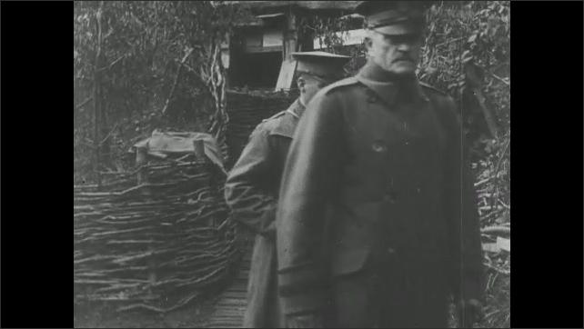 1910s: Soldiers walk down food line, get food. Military officers enter camp, salute. Man speaks.