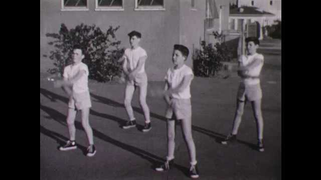 1950s: Young men perform exercises in unison.