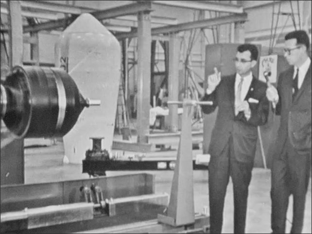 1960s: Model of spacecraft spins in test in NASA Goddard Space Flight Center lab. Two men stand next to model undergoing test, talking into microphone.
