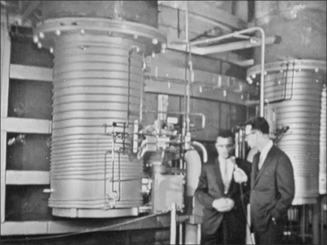 1960s: Two men look at equipment in lab at NASA Goddard Space Flight Center while talking into microphone, then walk towards other equipment while talking.
