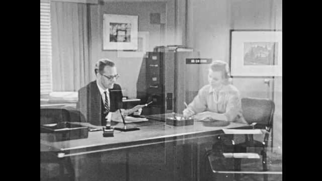 1950s: Woman sits next to desk. Man at desk speaks to woman, woman takes notes. Woman gets up, turns around, talks to man.