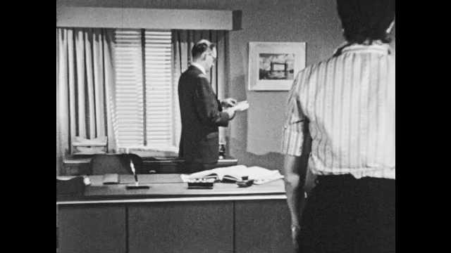1950s: Man stands behind desk, women enter room, sit next to desk. Woman stands up, starts talking. Man talks.