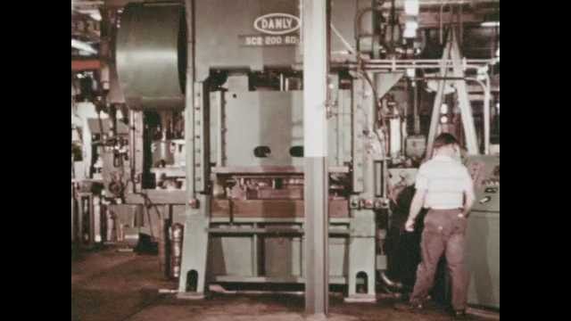 1970s: Large machines move up and down in manufacturing factory. Workers checking machine calibration. Washers being manufactured and placed on rod. Factory worker assembles metal parts.