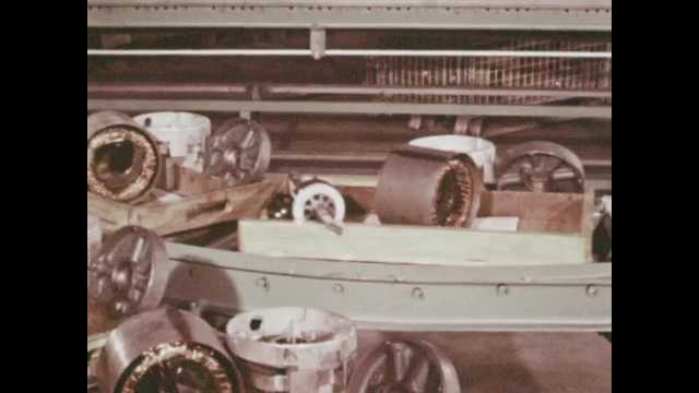 1970s: Levels of conveyor belts with parts on it in factory. Woman walks up to conveyor belt and picks up parts. Workers assemble motors in factory.