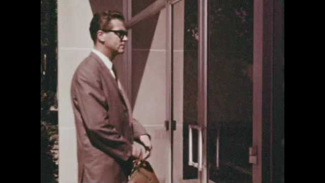 1970s: Man in suit and glasses holding briefcase walks into building. Man scrapes at outdoor motor as two men watch. Amusement park roller coaster filled with people moves on track.