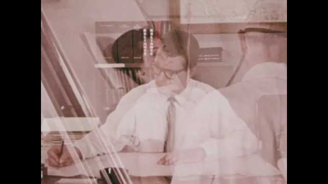 1970s: Man in suit and glasses sits at desk writing. Man addresses the camera.