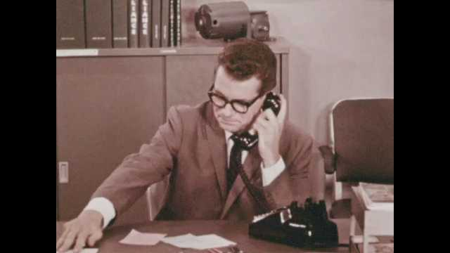 1970s: Man in suit and glasses sits at desk and dials telephone. Man talks on phone and smiles. Man takes notes.