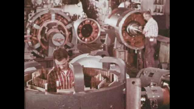 1970s: Engineers stand in the middle of and assemble large motors. Engineer hammers at center of motor in factory.