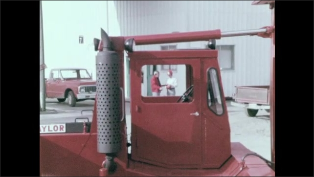 1970s: Taylor lift truck parked in yard. Two men stand and make notes on a clipboard.