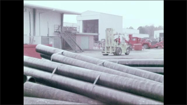 1970s: Green forklift travels at a safe speed on a construction lot. Forklift brakes before hitting a metal object in the lane.