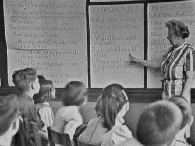 1960s: Teacher stands at front of class, points to notes on wall. Girl stands up and reads notes. Children raise hands. Children stand up and talk.