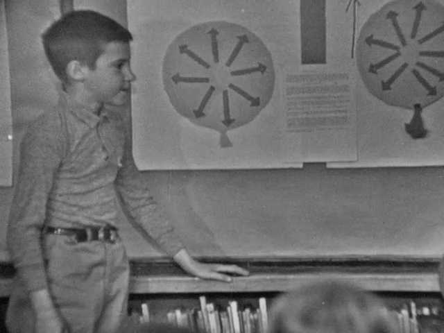 1960s: Two boys stand at front of class, one boy talks, the other boy holds and squeezes a balloon.