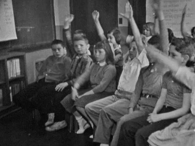 1960s: Children sit in chairs in classroom, raise hands. Girl stands up and talks. Woman stands at chalkboard, reads words written on large paper. Woman holds up vinyl record.