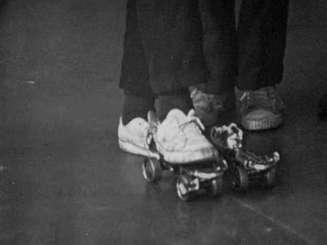 1960s: Boy stands on skates, pushes off, skates fly forward. Boys talk to teachers. Boy holds paper gun, pretends to shoot.