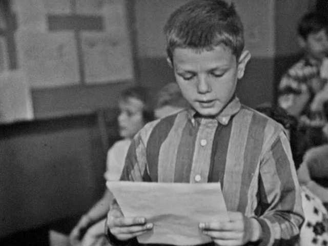 1960s: Boy stands up and reads.