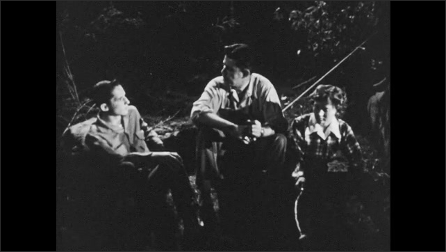 1950s: Campground at night. Man speaks, turning his head side to side. Man, teen boy and girl sit around a campfire. Man smokes pipe and speaks with the kids. Boy counts on his fingers.