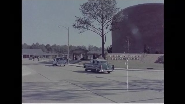 """1960s: Person holds up """"Williamsburg in Color."""" Cars drive by building. Sign on building for Colonial Williamsburg Information Center. Single brick building surrounded by brick wall."""