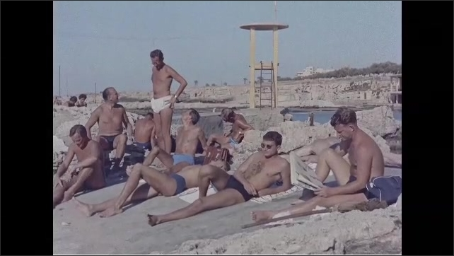 1960s: Men lay on beach. People sit at tables outdoors. Men stand and walk away.