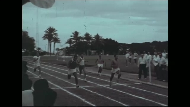 1960s: View of Olympic rings. Man at microphone, raises hand. Crowd by track, pan of runners crossing finish. Runners kneeling on track. Runners take off on track.