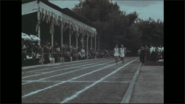 1960s: Men jogging on track by crowd. Man jumping over hurdle, falls.