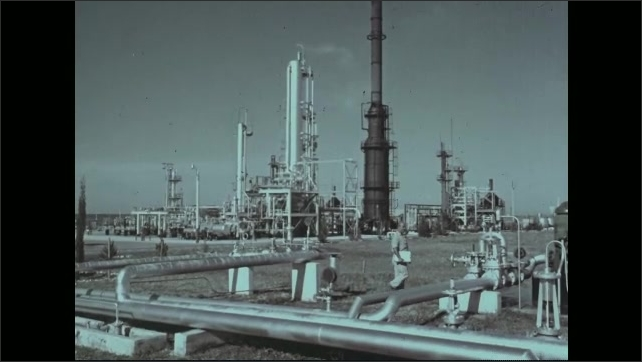 1960s: Exterior of oil refinery, man walks by pipes. Man inspecting pipes.