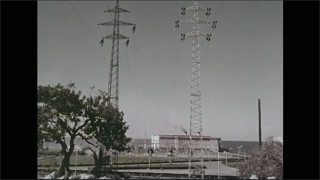 1960s: Truck drives from garage. Low angle shots of power lines. View of power station.