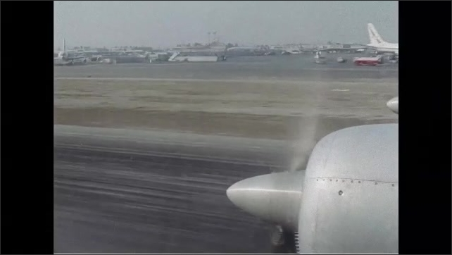 1960s: Flying in airplane coming down for landing, looking out window at ground below. Airplane lands. Person directs airplane on tarmac.