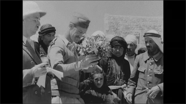 1940s: Men in uniform look at paper, point. Men fill bags with powdery substance. Man holds bouquet of flowers. Men and boy stand in crowd, look around.